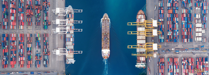 637816284 istock photo Aerial view panoramic oil tanker moving pass sea port warehouse and container ship or crane ship working for delivery containers shipment. Suitable use for energy power or transport or import export to global logistics concept. 1057138856