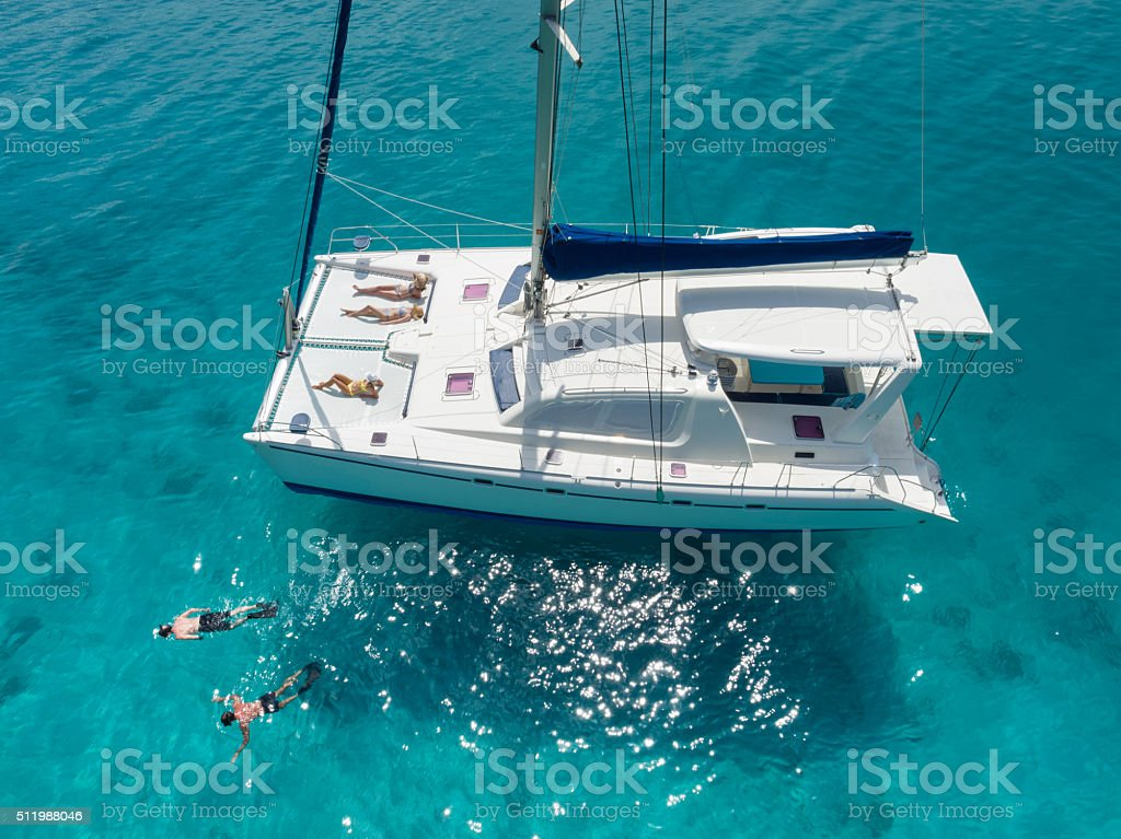 Aerial view people relaxing on catamaran anchored in tropical water stock photo