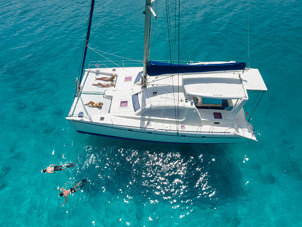 aerial view people relaxing on catamaran anchored in tropical water - katamaran bildbanksfoton och bilder