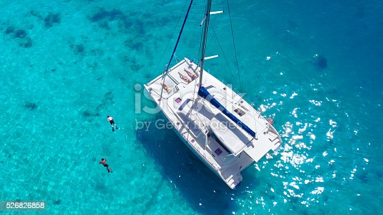 544966382istockphoto Aerial view People relaxing on Catamaran anchored in tropical water 526826858