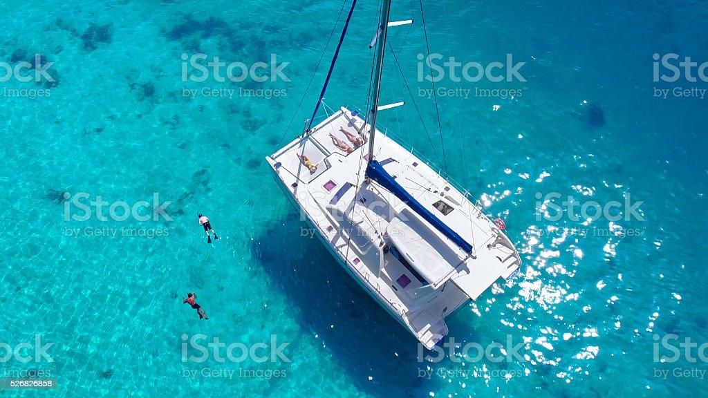 Вид с воздуха людей, расслабляющий на катамаране, стоящие на якоре в тропической воде стоковое фото