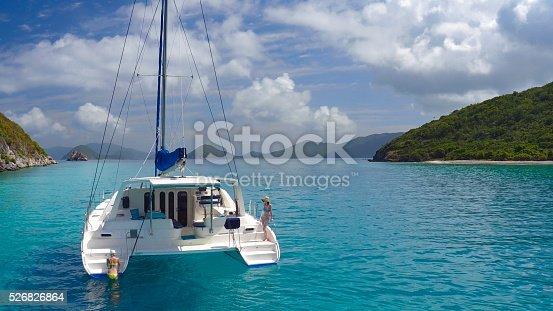544966382istockphoto Aerial view People relaxing on Catamaran anchored in tropical water 526826864