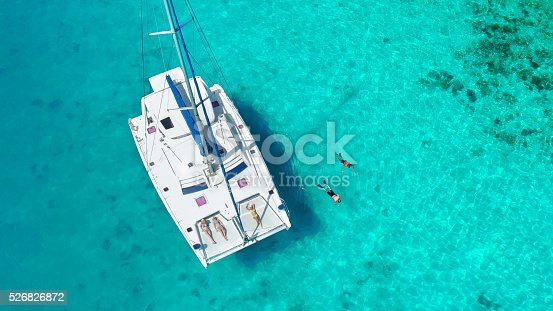 1066331604istockphoto Aerial view People relaxing on Catamaran anchored in tropical water 526826872