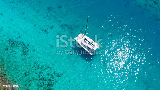 544966382istockphoto Aerial view People relaxing on Catamaran anchored in tropical water 526826884