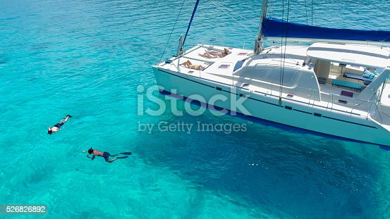 544966382istockphoto Aerial view People relaxing on Catamaran anchored in tropical water 526826892