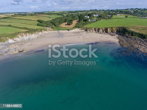 1130689824 istock photo Aerial view Porthcurnick beach bay Cornwall by drone 1168446922