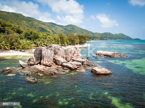 Aerial view over Anse Bateau with the typical Seychellois Granite Rock formations in the natural coral lagoon and sandy beaches on beautiful Praslin Island, Seychelles Islands, Africa