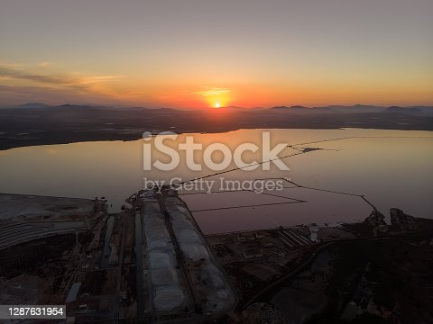 Aerial view salt lake of Las Salinas in Torrevieja city during sunset evening sky glowing sun over horizon, salt production industry concept. Costa Blanca, Alicante province. Spain