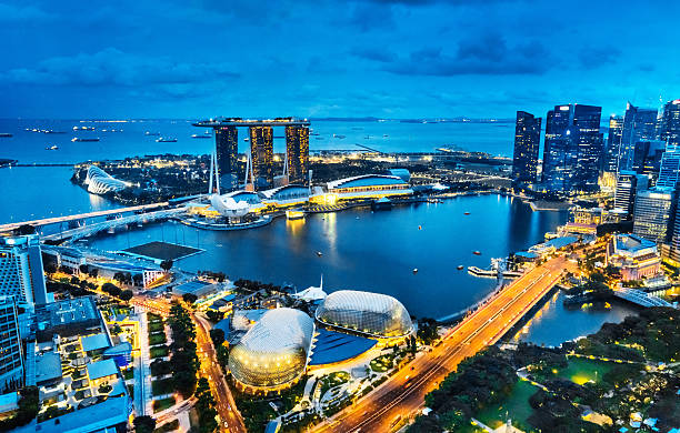 aerial view singapore, marina bay at dusk - singapore stock photos and pictures
