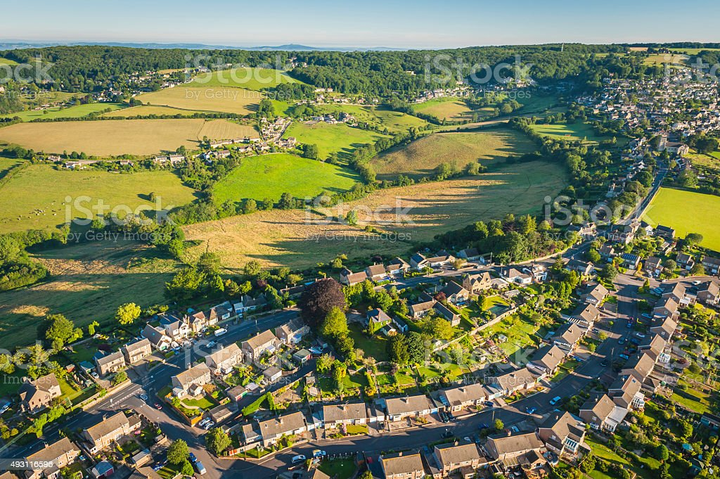 Aerial view suburban houses streets gardens surrounded by green countryside stock photo