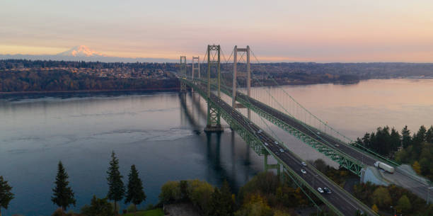 Aerial View Tacoma Narrows Bridges over Puget Sound Mount Rainier in the background Traffic makes way across the bridge over Puget Sound in Washington State between Tacoma and Gig Harbor gig harbor stock pictures, royalty-free photos & images