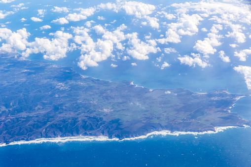621114928 istock photo Aerial view through the airplane window 1203078637