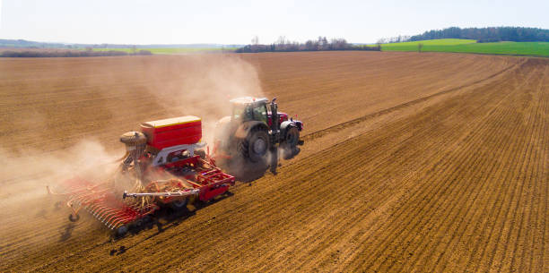 Aerial view to a Tractor with sowing machine working on a  field. Agriculture from above. stock photo