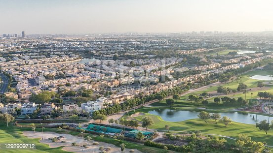 Aerial view to houses and villas with Golf course with green lawn and lakes timelapse. Traffic on streets. Warm evening light