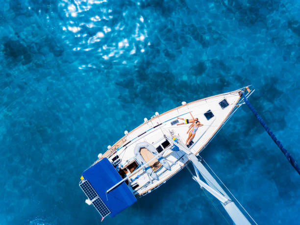 Aerial view to Yacht in deep blue sea. Drone photography stock photo