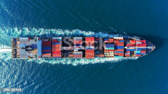 istock Aerial view Top speed with beautiful wave of container ship full load container with crane loading container for logistics import  export or transportation concept background. 1066762856