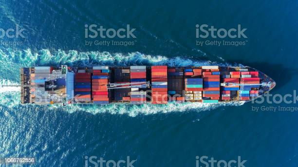 Photo of Aerial view Top speed with beautiful wave of container ship full load container with crane loading container for logistics import  export or transportation concept background.