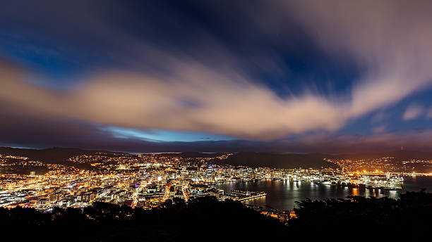 Aerial View Wellington City New Zealand at Night Aerial view of Wellington, the Capital City of New Zealand, at Night. Long exposure with stunning motion blurred cloudscape, wide angle shot from top of Mount Victoria. Wellington, North Island, New Zealand. mt victoria canadian rockies stock pictures, royalty-free photos & images