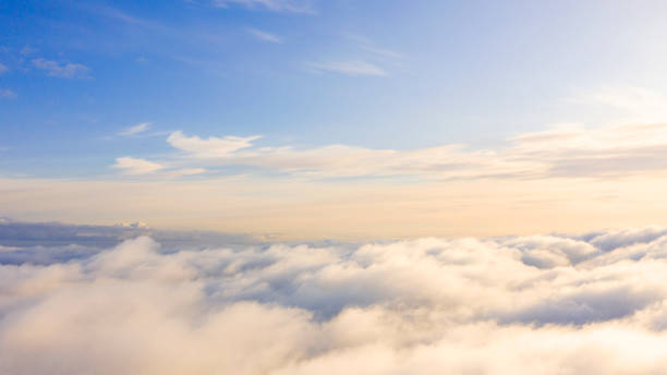 Aerial view White clouds in blue sky. Top view. View from drone. Aerial bird's eye view. Aerial top view cloudscape. Texture of clouds. View from above. Sunrise or sunset over clouds stock photo