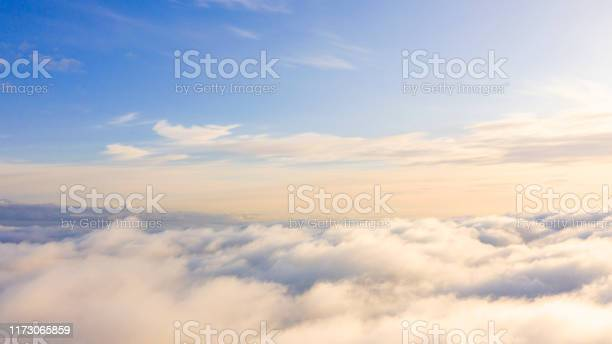 Photo of Aerial view White clouds in blue sky. Top view. View from drone. Aerial bird's eye view. Aerial top view cloudscape. Texture of clouds. View from above. Sunrise or sunset over clouds