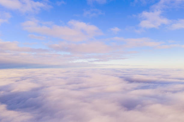 Aerial view White clouds in blue sky. View from drone. Aerial top view cloudscape. Texture of clouds. View from above. Sunrise or sunset over clouds. Panorama clouds stock photo