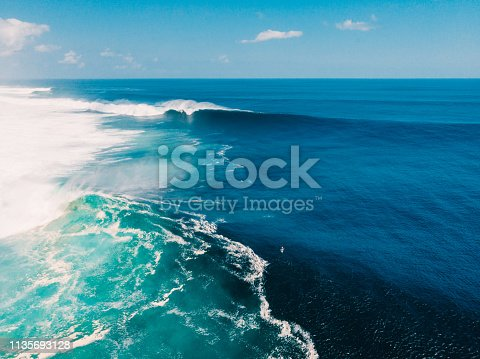 843079528istockphoto Aerial view with big blue wave for surfing. Big waves in ocean 1135693128