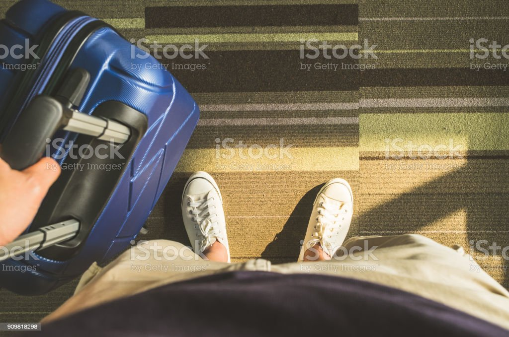 Aerial view,Looking down at white sneaker and travel suitcase with morning sunlight through window at airport terminal,Vacation concept stock photo