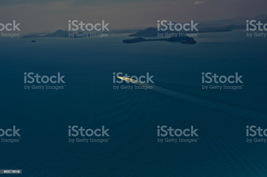 Aerial views east across Phang Nga Bay, Phuket, Thailand towards Phuket island with a lone speed boat seen in the vastness of the sea. stock photo
