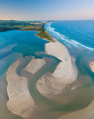 Aerial views of the sand patterns and textures and varying depths of the ocean inlet