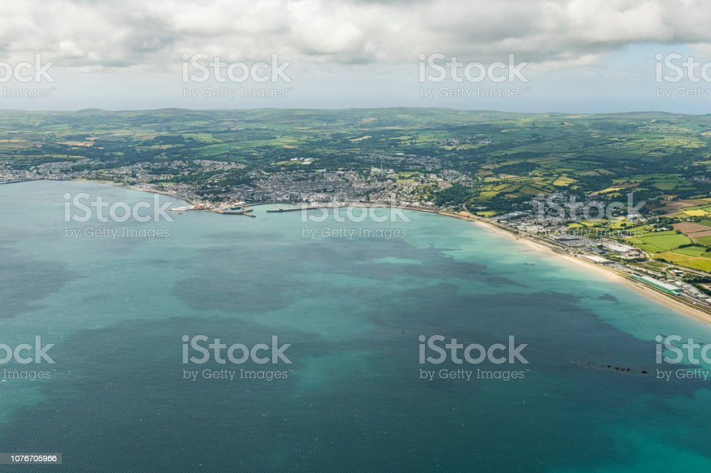 Aerial views over the sea to Penzance, Newlyn and Mousehole, Cornwall on a bright sunny June day. stock photo