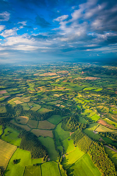 Aerial vista across green summer landscape under big country skies Big skies, dappled sunlight and dramatic clouds above an idyllic patchwork summer landscape of rolling hills, lush green farmland and country villages. ProPhoto RGB profile for maximum color fidelity and gamut. south wales stock pictures, royalty-free photos & images