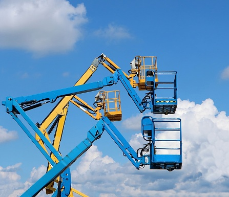 Four aerial work platforms against blue sky with fluffy clouds.