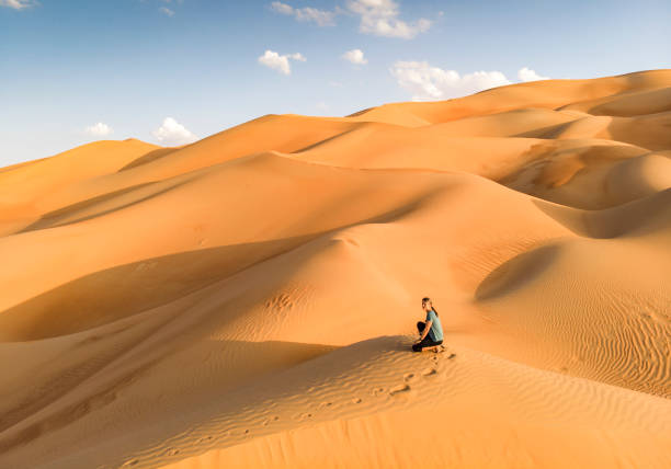 aeril view of a person in Liwa desert, part of Empty Quarter, the largest continuous sand desert in the world stock photo