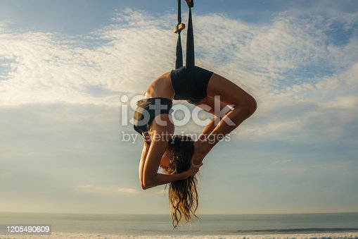 istock aero yoga beach workout - young attractive and athletic woman practicing aerial yoga exercise training acrobatic  body postures on blue sky over sea in Bali island healthy lifestyle concept