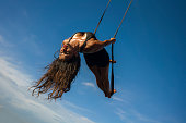 """aero yoga beach workout - young attractive and athletic woman practicing aerial yoga exercise training acrobatic  body postures on blue sky over sea in Bali island healthy lifestyle concept""""n"""