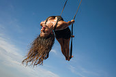 aero yoga workout - young attractive and athletic woman practicing aerial yoga exercise training acrobatic  body postures isolated on blue sky in balance flexibility control and healthy lifestyle