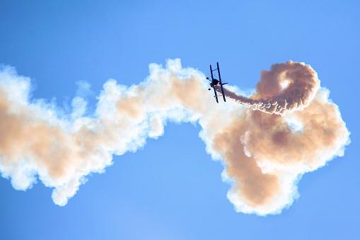 Aerobatic biplane on the blue sky