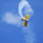 Biplane performing aerobatic stunt. Paint scheme of WWII Army Air Corp trainer. Stearman Kaydet.