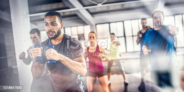 Fitness group shadow boxing with dumbbells during an aerobics class.