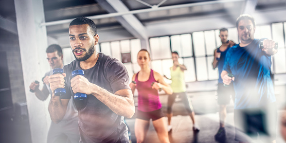 istock Aerobics class shadow boxing with dumbbells 1018647930
