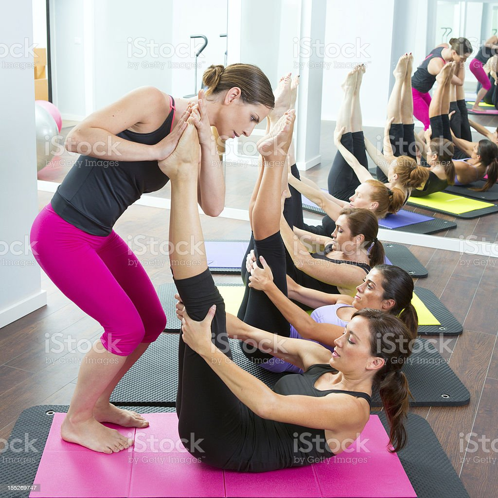 Aerobics Pilates personal trainer helping women group stock photo