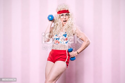 An aerobics class instructor from the late 1980's - early 1990's poses for a portrait, her long blond hair styled with a big perm.  She exercises with small dumbbells, getting a good cardio workout in.  Pink striped background.