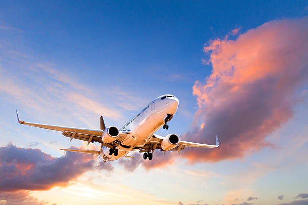 aeroplane coming in to land at sunset - vliegtuig stockfoto's en -beelden