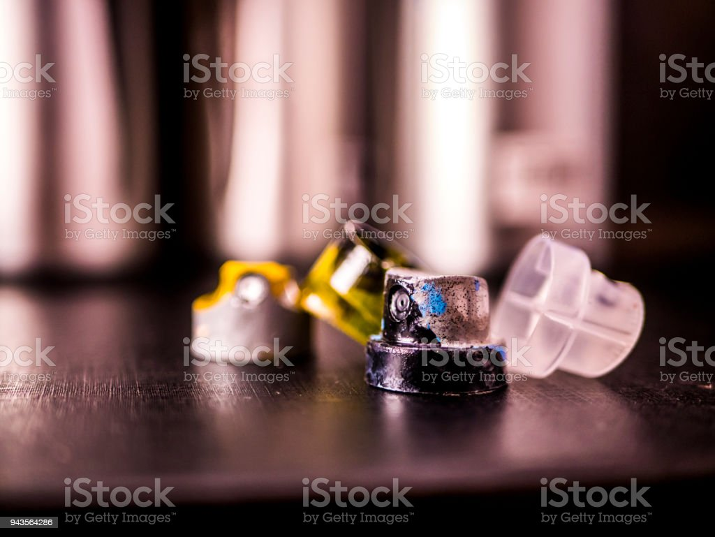 aerosole spray paint caps and cans on black surface stock photo