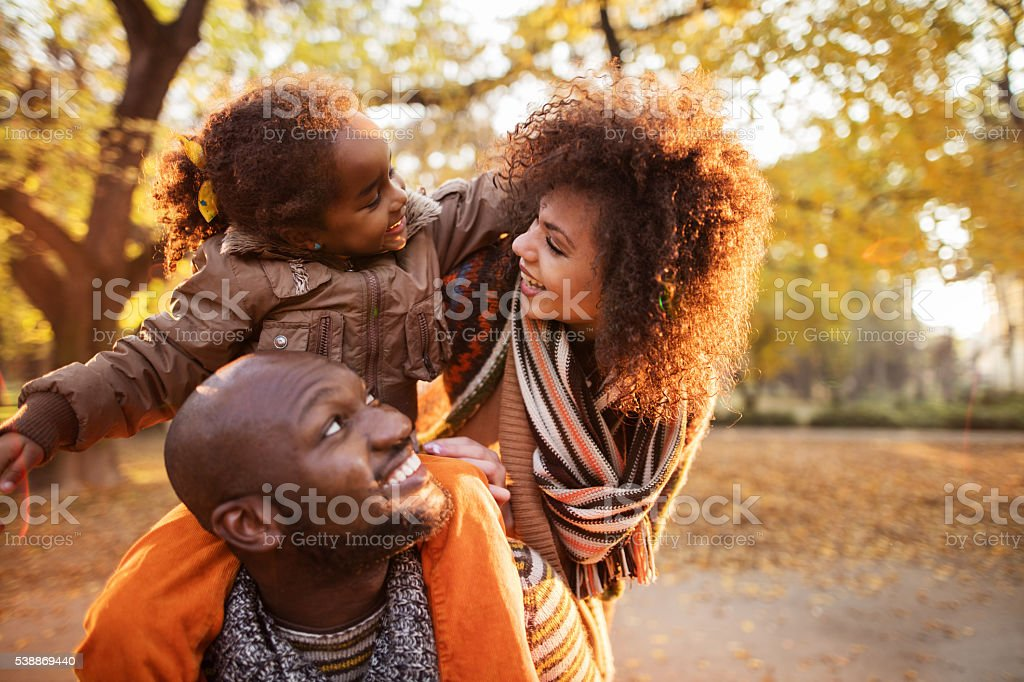 Affectionate African American family enjoying in autumn park. stock photo
