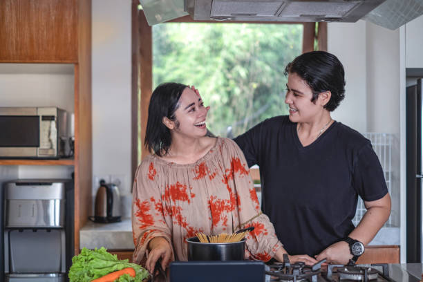 Affectionate androgynous female stroking her wife hair Shot of affectionate androgynous female stroking her wife hair while cooking together cisgender stock pictures, royalty-free photos & images
