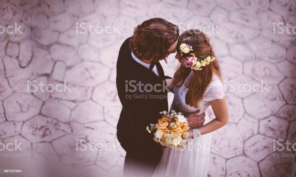 Affectionate bride and groom embracing and dancing at wedding reception stock photo