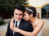 Affectionate bride embracing groom and smiling