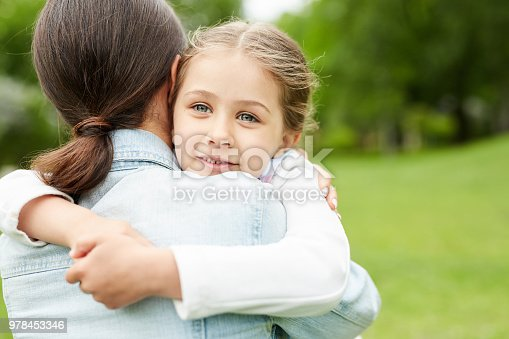 Cute girl embracing her mother while spending time with her in park