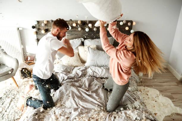 bekämpfung von zärtlich paar und kissen im schlafzimmer - kissenschlacht paar stock-fotos und bilder